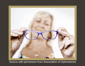 Picture of an older lady holding up her new spectacles